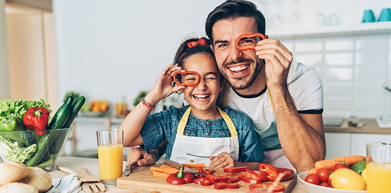 Dad and daughter cutting veggies
